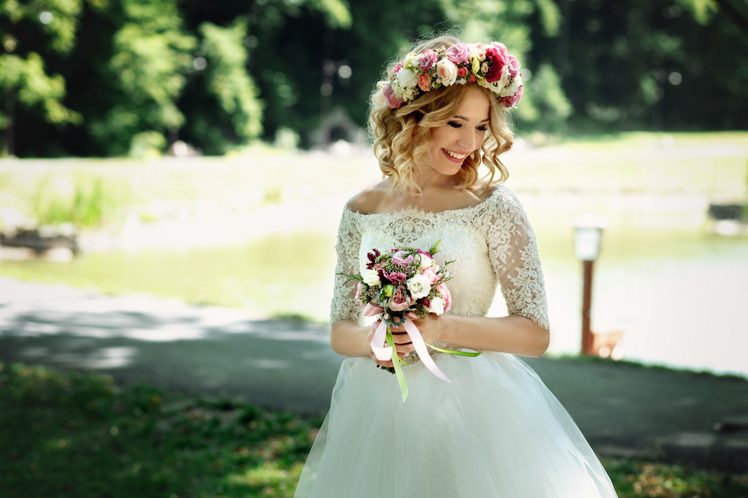 Beautiful blonde happy bride in elegant white dress in a wreath with bouquet outdoors